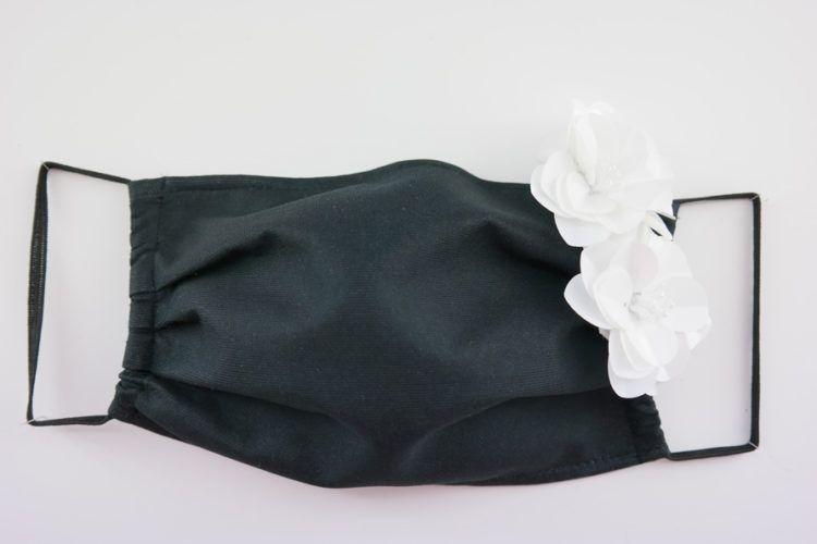 Mascarilla negra con alfiler de flor