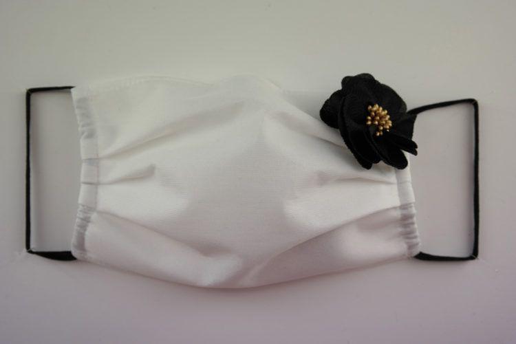 Mascarilla blanca con flor de tela de color negro
